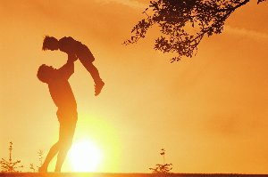 Man Lifting a Child in the Air in Front of a Sunset
